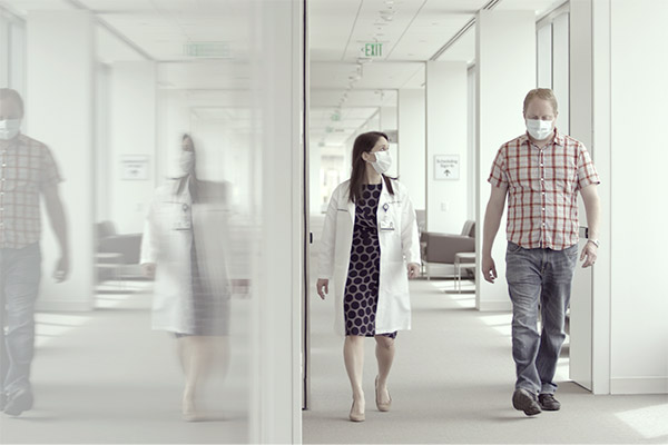 Female cancer provider walking and talking to male patient while wearing masks