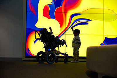 Children play in front of the interactive wall of monitors at the new Cleveland Clinic Children's outpatient center.