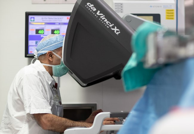 Surgeon sits at robotic surgical console