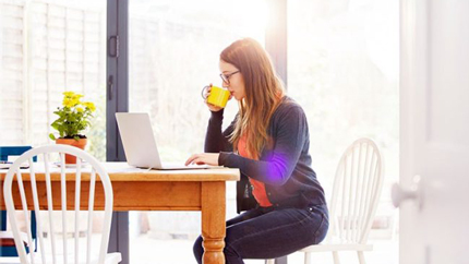Woman sitting at kitchen talbe sipping coffee while working