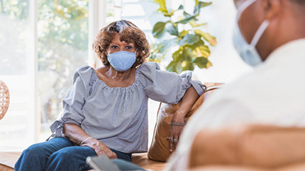 Woman sitting on couch with mask talking to her husband
