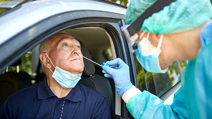 Older man receiving COVID-19 test in car from healthcare professional