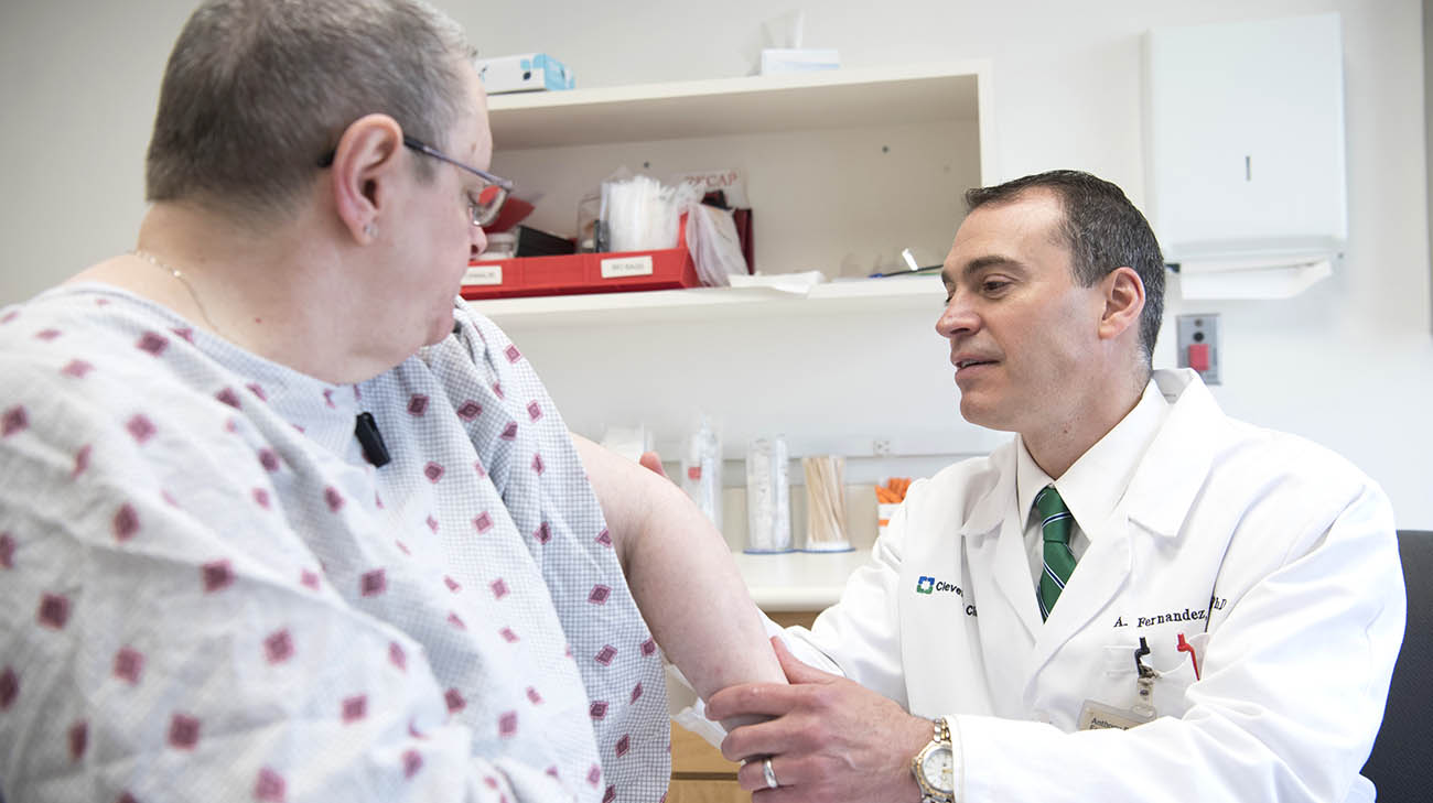 Dr. Anthony Fernandez examines patient's classic dermatomyositis skin condition.