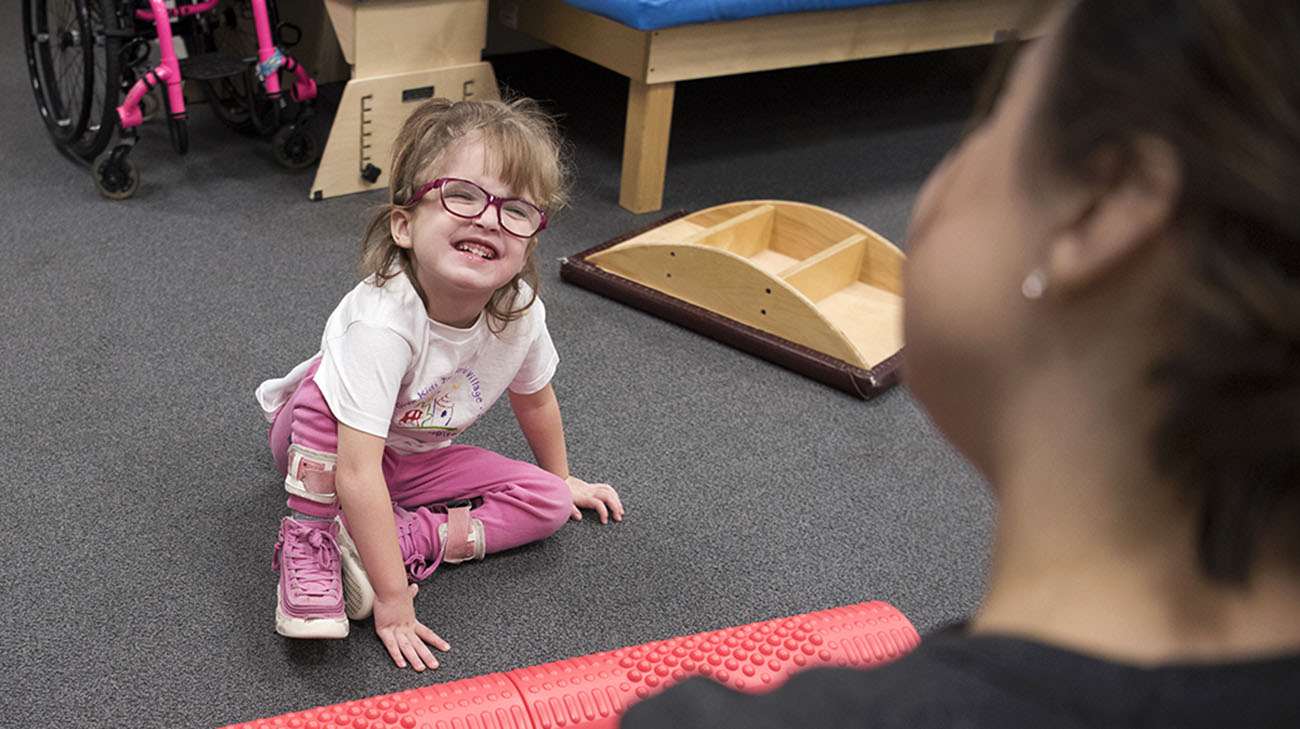 Kaylee smiles up at her physical therapist. (Courtesy: Cleveland Clinic)