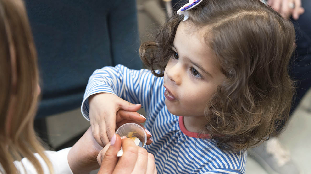 Harper eating cashew butter during one of her test sessions at Cleveland Clinic Food Allergy Center of Excellence.
