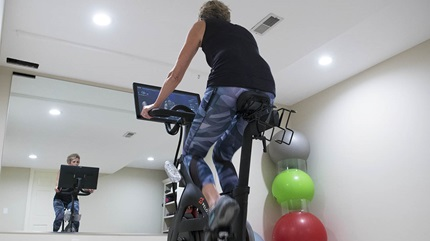 Sally riding her stationary bike at home.