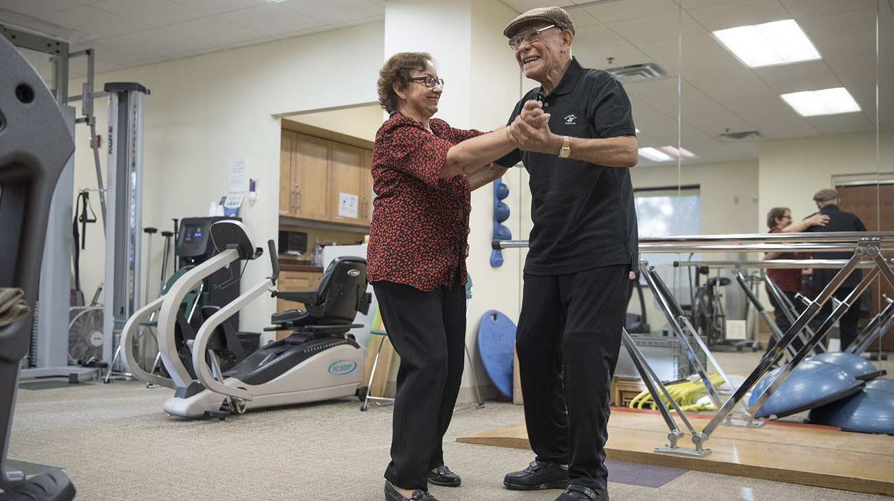 Angel and his wife, Raquel, dance at a physical therapy appointment.