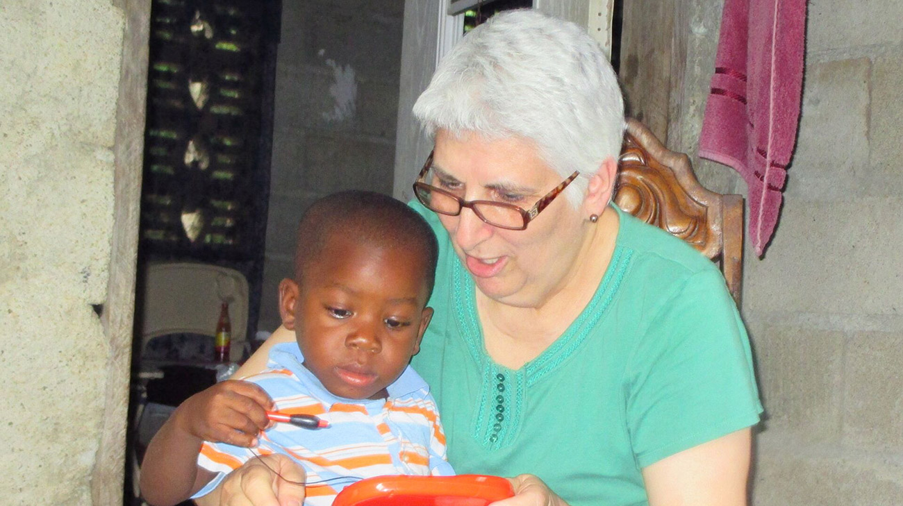 Jane with Sammy, 5, an orphan in Haiti she and her husband raised as one of their own. (Courtesy: Jane Dennington)